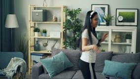 Piękna młoda dama tanczy w domu i śpiewa będący ubranym hełmofony i słuchanie muzyczny w żywym pokoju samotnie zdjęcie wideo