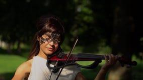 Piękna młoda dziewczyna bawić się na elektrycznym skrzypce na pięknym parku zbiory wideo