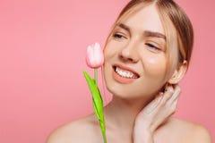 Piękna młoda dziewczyna z czystą skórą, trzyma różowego kwiatu blisko twarzy na różowym tle, zdjęcia stock