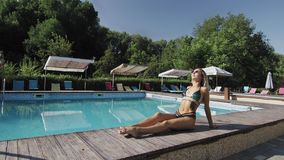 Piękna młoda kobieta w okularach przeciwsłonecznych sunbathing na krawędzi basenu zbiory