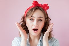 Piękna młoda kobieta z szpilki fryzurą i makijażem Studio strzał na różowym tle obraz stock