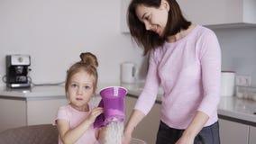 Piękna młoda mama wpólnie i jej śliczny mały córki narządzania ciasto Mała dziewczynka używa mąka odsiewacza w kuchni zbiory wideo
