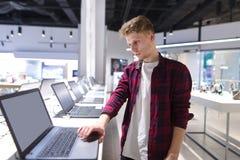 piękna młoda nabywca wybiera laptop w nowożytnym elektronika sklepie obrazy stock