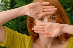 Piękna młoda rudzielec kobieta chuje za rękami fotografia royalty free