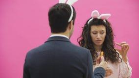 Piękna młodej dziewczyny pozycja na różowym tle Podczas to, tam są ucho króliki na głowie Mężczyzna stojaki zbiory wideo