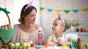 Piękna matka i córka w śmiesznych kapitałkach je Wielkanocnych czekoladowych jajka obrazy stock