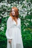 Piękna miedzianowłosa dziewczyna w białej sukni wśród kwitnąć jabłonie w ogródzie zdjęcia royalty free
