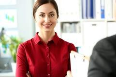 Piękna uśmiechnięta dziewczyna w czerwonej bluzce przy miejsce pracy patrzeje in camera fotografia royalty free
