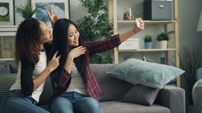 Piękne młode damy patrzeje ekran, ono uśmiecha się i pozuje dla kamery biorą selfie z smartphone w domu, młodość zbiory