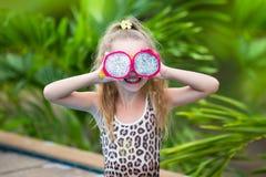 Pięknego dziecka dziewczyna bawić się z smok owoc blisko basenu Tropikalny plenerowy tło kosmos kopii zdjęcia royalty free