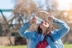 Pięknej młodej dziewczyny słuchająca muzyka outdoors zdjęcie royalty free