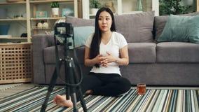 Pięknej młodej kobiety rozochocony vlogger jest opowiadający magnetofonowego wideo z kamerą dla interneta bloga i gestykulujący D zdjęcie wideo