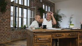 Piękni środkowi rok kobiety siedzi przy drewnianym biurkiem pracuje z papierowymi dokumentami w szkłach gdy jej mały uroczy zdjęcie wideo
