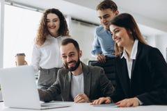 Piękni ludzie biznesu używają komputery i one uśmiechają się podczas gdy pracujący w biurze obraz stock