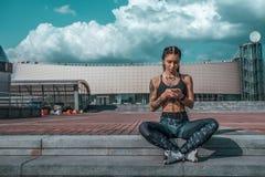 Piękni młoda dziewczyna tatuaże, lata miasta ręki smartphone słuchają muzycznych hełmofony, sportswear Siedzi na krokach bezpłatn obraz royalty free