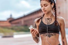 Piękni młoda dziewczyna tatuaże, lata miasto, ręki smartphone słuchają muzycznych hełmofony Online zastosowanie na internecie zdjęcie stock