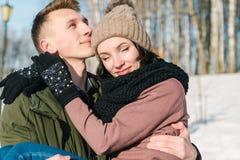 Piękni potomstwa dobierają się w miłości w parku na jasnym pogodnym zima dniu Młody człowiek trzyma jego dziewczyny obraz royalty free