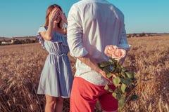 Piękny i potomstwo dobiera się mężczyzny i kobieta, w lecie w pszenicznym polu za prezentem, jest bukietem kwiaty, niespodzianka  obraz royalty free