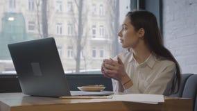 Piękny kobiety główkowanie i patrzeć w nadokiennej trzyma filiżance w rękach zamykamy w górę Ładna kobieta cieszy się ona gorąca zdjęcie wideo