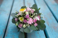 Piękny kwiatu przygotowania z białym eustoma, kiści róże, goździki w nowej herbacianej filiżance na drewnianym stole obrazy royalty free