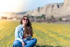 Piękny młodej dziewczyny obsiadanie na trawie Plenerowej fotografia stock