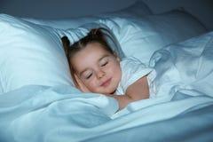 Piękny małej dziewczynki dosypianie w łóżku przy nocą bedtime obrazy royalty free