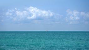 Piękny seascape z białą żeglowanie łodzią po środku morza i niebieskim niebem z chmurami obraz stock
