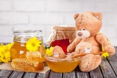 Piękny skład miodowi produkty, miód, honeycombs, perga i lato, kwitnie na drewnianym stole z misiem, obrazy royalty free