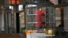Piękny szklany candlestick z dużą czerwoną palenie wosku świeczką czerwony kolor który jest wśrodku candlestick i stoi dalej zbiory wideo