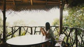Piękny tło strzał młoda szczęśliwa turystyczna kobieta cieszy się ranek kawę przy zadziwiającym tropikalnym lasowym hotelu tarase zbiory wideo