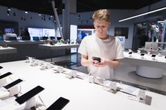 Piękny uczeń w koszulki białych spojrzeniach przy smartphones w elektronika sklepie Kupuje telefon komórkowego w sklepie fotografia stock