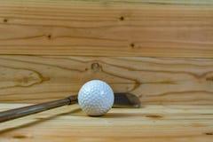 Piłka golfowa i kij golfowy na drewnianej podłodze zdjęcie royalty free
