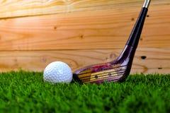 Piłka golfowa i kij golfowy na trawie z drewnianą ścianą obraz royalty free