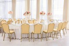 Pièce admirablement décorée avec les tables couvertes avec des fleurs dans le restaurant pour la célébration du mariage Photos stock