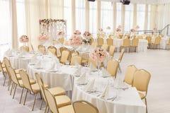 Pièce admirablement décorée avec les tables couvertes avec des fleurs dans le restaurant pour la célébration du mariage Photographie stock