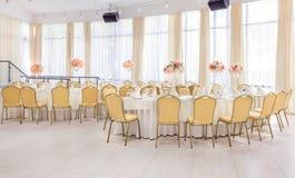 Pièce admirablement décorée avec les tables couvertes avec des fleurs dans le restaurant pour la célébration du mariage Photo libre de droits