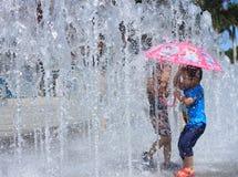 Pièce asiatique de gosses de remorquage par la fontaine d'eau Photo libre de droits