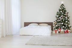 Pièce blanche de décor avec des cadeaux de Noël de nouvelle année de lit Images libres de droits
