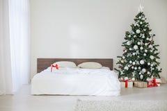 Pièce blanche de décor avec des cadeaux de Noël de nouvelle année de lit Photographie stock libre de droits