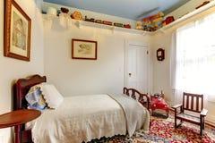 Pièce blanche lumineuse de garçons avec le lit, la chaise de basculage et le coloufu en bois Images libres de droits