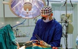 Pièce chirurgicale dans l'hôpital avec l'équipe médicale des chirurgiens faisant des interventions chirurgicales envahissantes mi images stock
