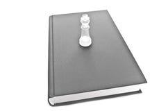 Pièce d'échecs en verre sur le livre Photographie stock libre de droits