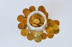 Pièce d'or dans la bouteille en verre sur le fond blanc Photo libre de droits