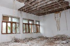 Pièce dans le bâtiment abandonné avec les fenêtres cassées et l'isolation accrochante de plafond Photo libre de droits