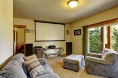 Pièce de cinéma dans la maison américaine avec l'écran de projecteur sur le mur photos libres de droits