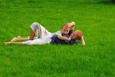 Pièce de deux garçons sur l'herbe Photographie stock