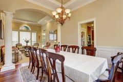Pièce de Dinning avec la grands table et un bon nombre de chaises Photographie stock