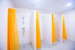 Pièce de douche publique avec plusieurs douches Grande, légère, vide pièce de douche publique, avec les murs lumineux et le planc Image libre de droits