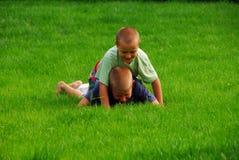 Pièce de garçons sur l'herbe Images libres de droits
