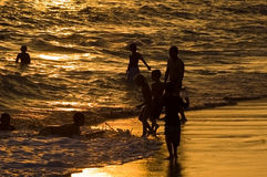 Pièce de gosses dans la vague déferlante au coucher du soleil Photos stock